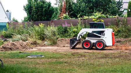 A skid steer loader clears the site for construction. Land work by the territory improvement. Machine for work in confined areas. Small tractor with a bucket for moving soil, turf and bulk materials. Stockfoto