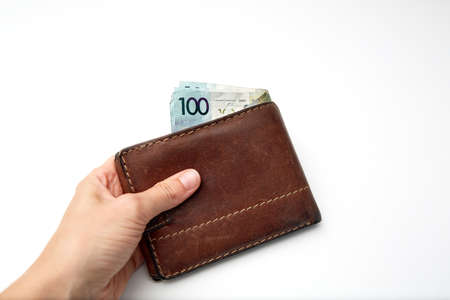 Wallet with paper money in hand isolated on white background. Banknote of one hundred Belarusian rubles. Minimal salary. Living wage budget. Close-up. Offline payments. Cash payment. Financial credit. Stockfoto