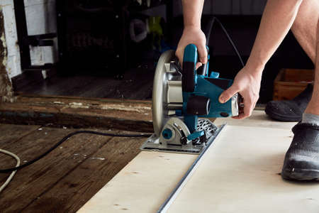 Sawing plywood by circular saw. Home repair. Hand tool. Man hold equipment. Building process. Woodworking. Safety engineering. Without gloves. Copy space. Indoor. Cutting material. Rental instrument.