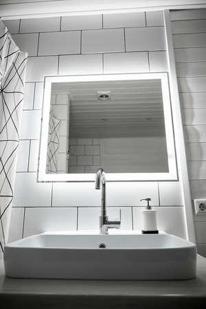Bathroom in white color. Large washbasin.