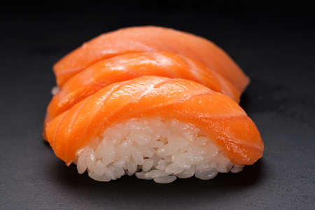 Sushi and rolls. Rolls for the Asian menu.On a black background. Raw fish and rice. Shrimp, salmon, squid, caviar