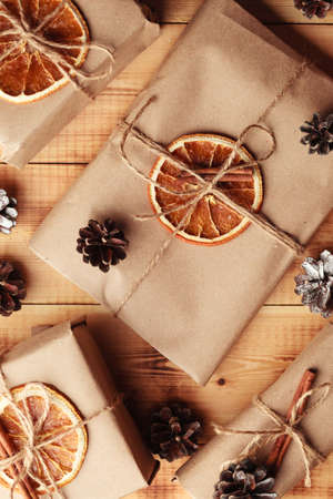 Gifts for Christmas and New Year. packed craft gifts with cinnamon and orange for decoration.