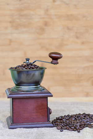Coffee grinder full of roasted coffee beans and coffee beads on the left side