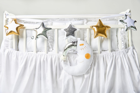 Silver, gold and white star shaped pillows and sleeping moon cushion on a white baby cot Stock Photo