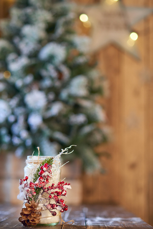 White Christmas candle holder decorated with pine cone and ashberry stick under Christmas tree on a wooden table