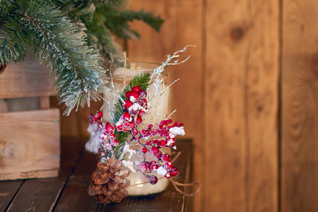 White candle holder decorated with pine cone and red ashberry under Christmas tree on a wooden background Stock Photo