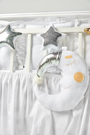 Gold and white star shaped pillows and sleeping moon cushion on a white baby cot