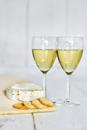 Glass of white wine, camembert cheese and crackers on a wooden background - vertical Stock Photo