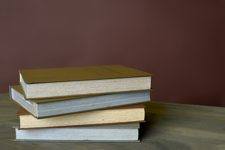 Four stamp albums books bunch on a wooden table and bordeaux background Stock Photo