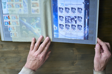 Senior man hands holding a postage stamp stamps collection, Gagarin and space theme, a wooden background Sajtókép