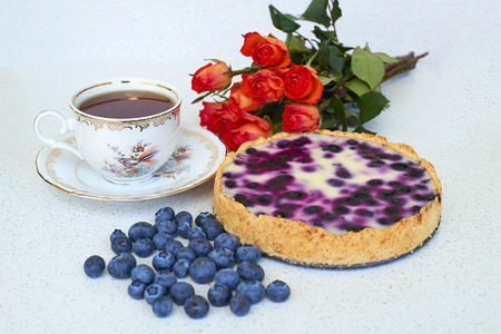 Blueberry pie, cup of tea, heap of blueberries and red roses on a white background - still life food Stock Photo