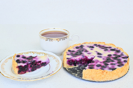 Blueberry pie, cup of black tea, piece of pie and three blueberries on a plate on a white background Standard-Bild