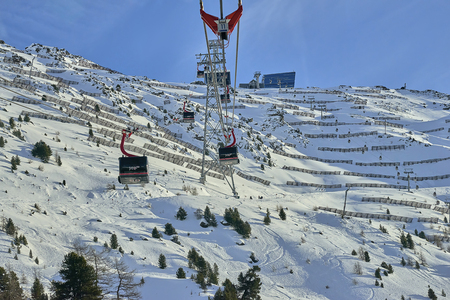 Ischgl, Austria - December 31, 2017: Going upward funfor gondola cable car on a mountain slope in a sunny winter day, ski resort in Tyrol Alps