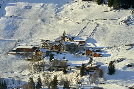Ischgl, Austria - January 01, 2018: Snow-covered mountain village on a sun-drenched hill slope in a sunny winter afternoon, Ischgl Tyrol Alps