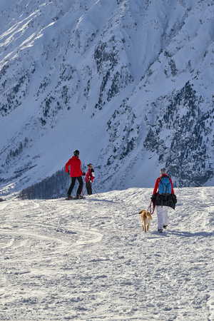 Ischgl, Austria - December 31, 2017: Woman walks with her dog on a mountain hill