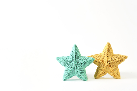 Yellow and blue-green knitted five-pointed star shaped pillows on white background - two pieces - mock up pattern