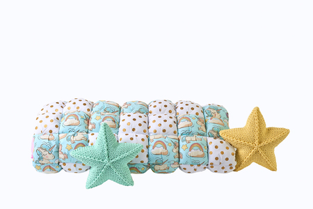 Yellow and blue-green knitted five-pointed star shaped pillows and patchwork comforter on white background