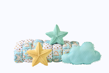 Yellow and blue-green knitted five-pointed star shaped pillows, patchwork comforter and cloud-shaped blue pillow on white background