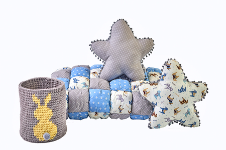 Two five-pointed star shaped pillows, patchwork comforter and knitted basket with yellow rabbit on white background