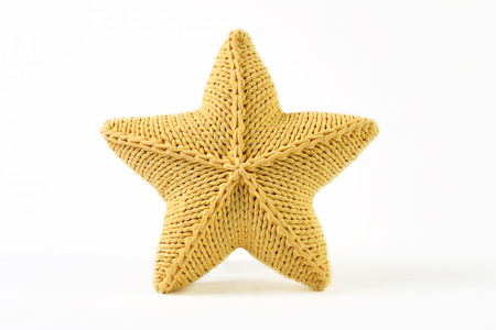 Yellow knitted five-pointed star shaped pillow on white background