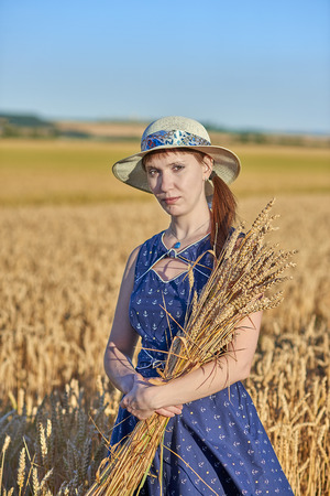 Young woman in blue dress with spikelets of wheat in wheat field - full face