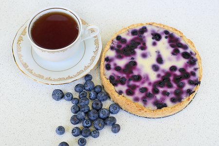 Cup of tea, blueberry pie and blueberries on a white background - above