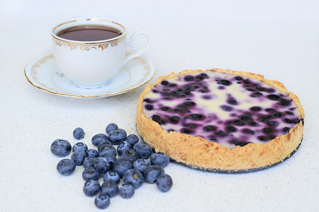 Cup of tea, blueberry pie and blueberries on a white background
