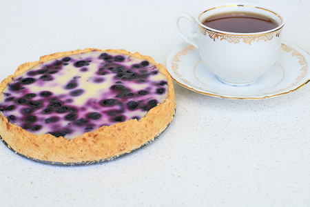 Cup of tea and blueberry pie on a white background - horizontal Standard-Bild