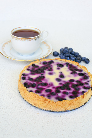 Cup of tea and blueberry pie on a white background - vertical