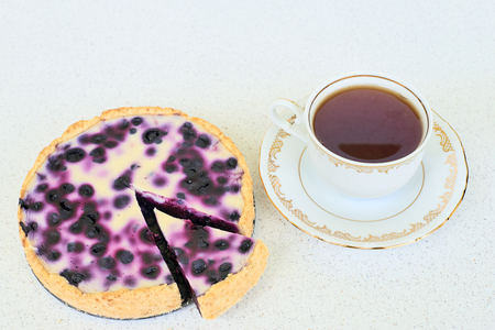Cup of tea and blueberry pie on a white background - high angle view