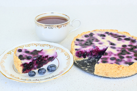 Cup of tea, piece of blueberry pie and blueberries on a white background - high angle view