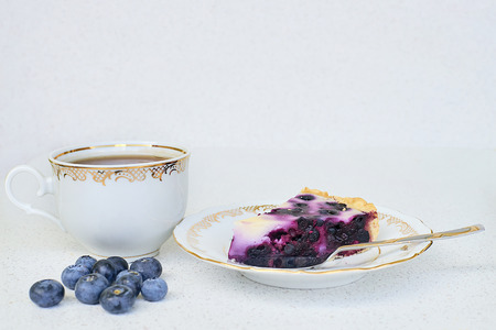 Cup of tea, piece of blueberry pie and blueberries on a white background - close up