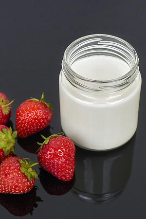 Glass jar with yogurt and six strawberries on a black background