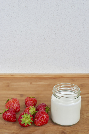 Glass jar with yogurt and seven strawberries on a wooden background Standard-Bild