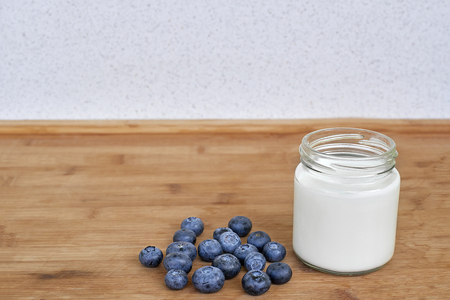 Yogurt in glass jar and blueberries on a wooden background