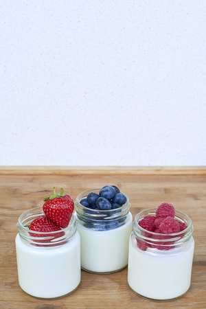 Three glass jars with yogurt and forest berries