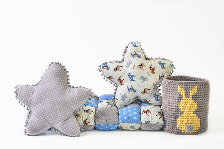 Two five-pointed star shaped pillows, patchwork comforter and knitted padded stool on white background