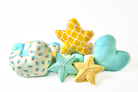 Yellow and blue knitted and stitched five-pointed star shaped pillow, patchwork comforter and heart shaped pillows on white background