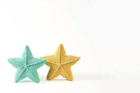 Yellow and blue-green knitted five-pointed star shaped pillows on white background - two pieces