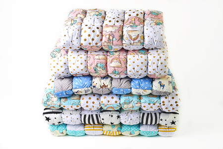 Patchwork and fashion concept - beautiful stack of colorful quilts, bedspreads stacked in several rows in height for storage, sale of stitched products on a white background Banque d'images - 98076048