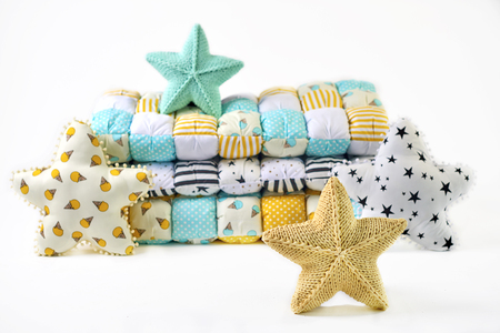 Yellow and blue-green knitted and stitched five-pointed star shaped pillows and patchwork comforter on white background