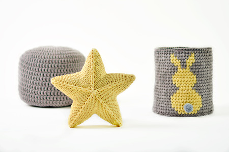 Yellow knitted five-pointed star shaped pillow, knitted basket with yellow rabbit and padded stool on white background