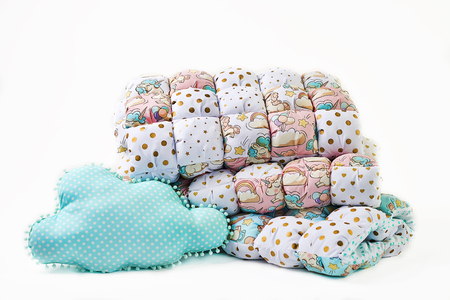Patchwork comforter and cloud shaped blue pillow on white background