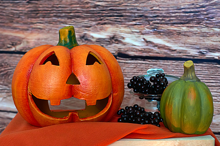 Halloween pumpkins and blackberry on the wood background