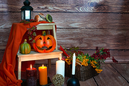 Halloween pumpkin, candles and mushrooms on wood background