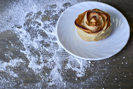 Delicious and sweet baked rose shaped pastry with apple filling on white plate on wooden background powdered with castor sugar