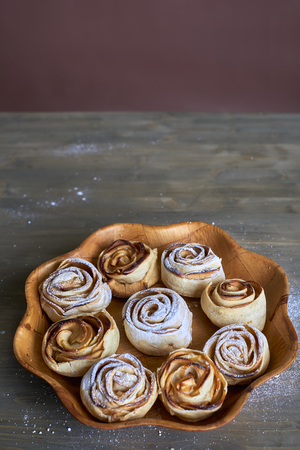 Delicious and sweet baked rose shaped pastry with apple filling on a wooden flower shaped plate on a wooden background