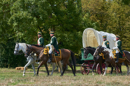 Slavkov u Brna, Czech Republic - August 11, 2018: Historical reenactment in Slavkov and Brna (Austerlitz). Horsemen are preparing to battle. Historical van is at background.