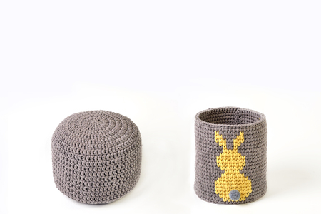 Knitted basket with yellow rabbit and padded stool on white background Stock Photo