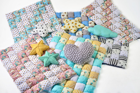 Bundle of colorful patchworked comforters with unicorn and stars design and pillows on white background